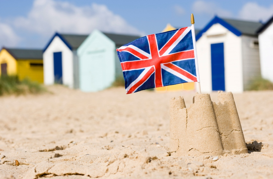British flag in sandcastle by beach huts